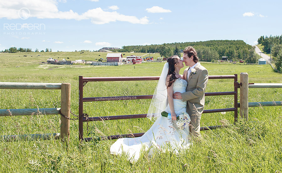Calgary wedding photo of couple near farm and rolling hills