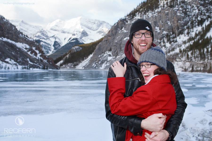 A couple with a red coat laugh beside a frozen lake in the Rocky Mountains