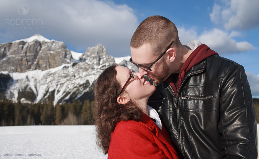 Rocky Mountains engagement photos kiss with a red wool coat