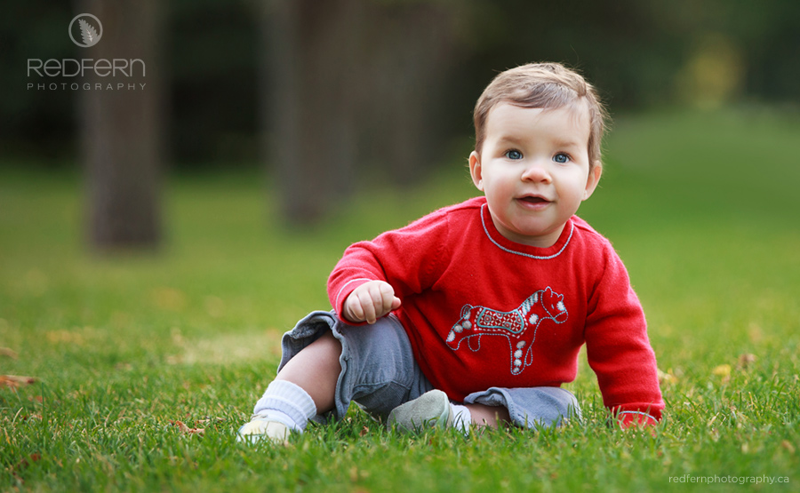 Cute Canadian Baby in the grass in a red sweater