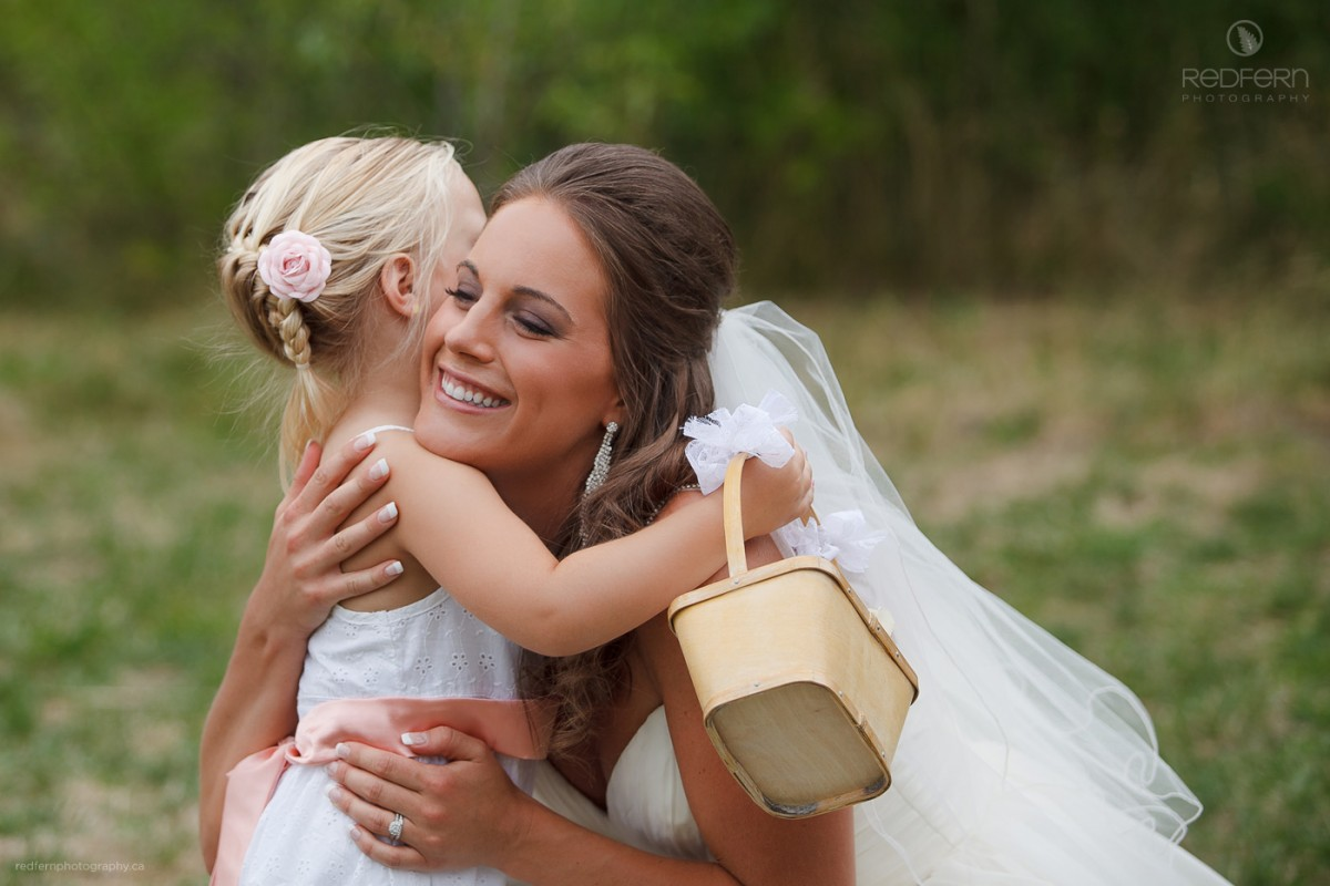 bride hugging flower girl after ceremony